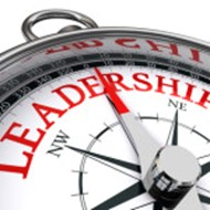 """Close up of a compass pointing towards the word """"leadership."""""""