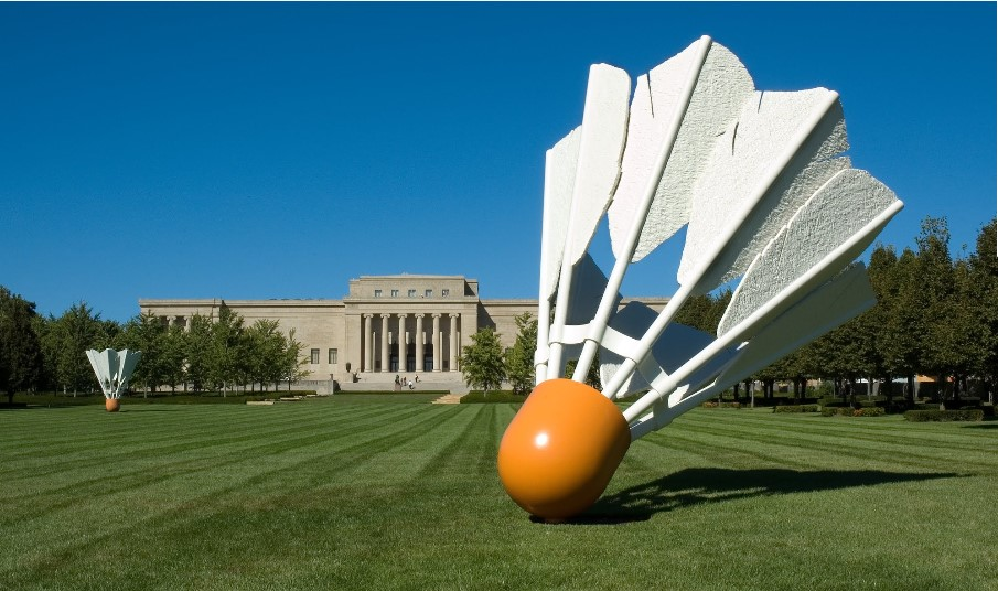 Image of the exterior of the Nelson-Atkins. There is a large sculpture of a birdie (badminton) in the foreground on a green lawn, with the art museum building in the background.