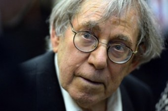 A close-up shot of a man looking towards the camera. He is an older man, white, with gray hair and wearing glasses.