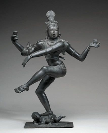 A photo of a dark gray, bronze statue against a gray background. The god Shiva raises his right leg and extends his four arms in a dance.