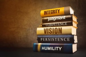 """A stack of leadership books against a plain background. The books have titles of key leadership words on their spines, like """"Integrity."""""""